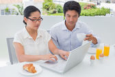 Smiling couple having breakfast together using laptop — Stock Photo