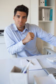Casual businessman frowning at camera at his desk — Stock Photo