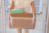 Fired businesswoman holding box of her things — Stock Photo