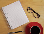 Overhead of notebook and glasses with pen and coffee cup — Stock Photo