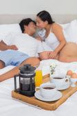 Affectionate couple having breakfast in bed — Stock Photo