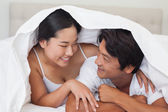 Happy couple lying on bed together under the duvet — Stock Photo