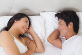 Happy couple lying in bed chatting — Stock Photo