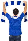 Football fan in blue holding scarf — Stockfoto