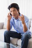 Annoyed man sitting on couch talking on phone — Stock Photo