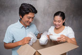 Happy couple unpacking moving boxes — Stock Photo