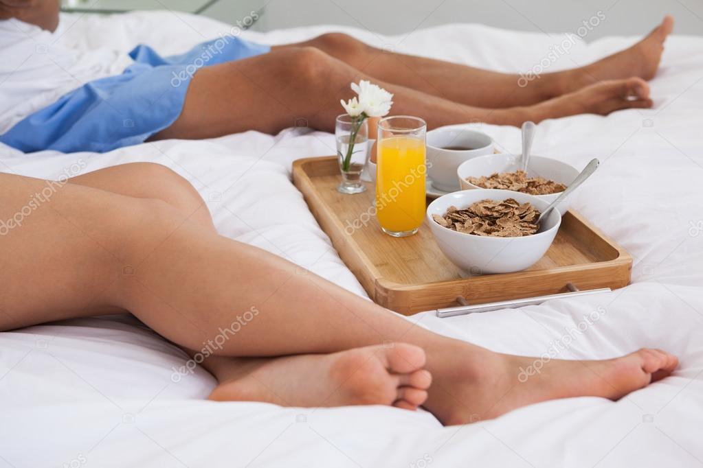 couple allong sur le lit avec petit d jeuner sur un plateau photo 45111557. Black Bedroom Furniture Sets. Home Design Ideas