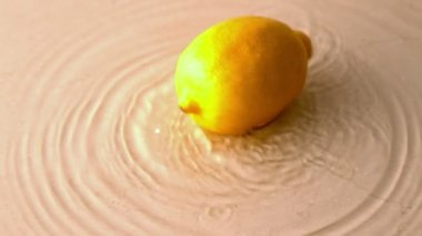 Lemon spinning on wet white surface — Stock Video