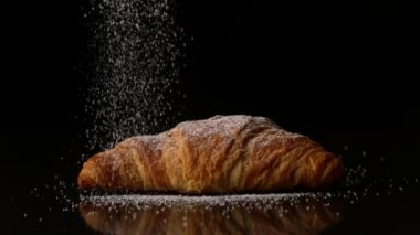 Powdered sugar sprinkling onto a croissant — Stock Video