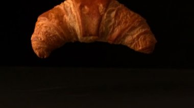 Croissant falling onto black surface — Stock Video