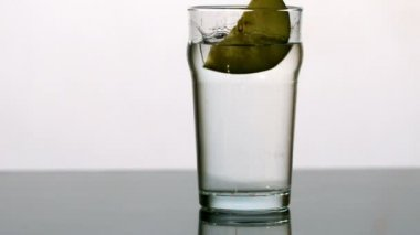 Apple wedge falling into pint of water — Stock Video