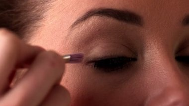 Woman applying eye shadow to eye — Stock Video