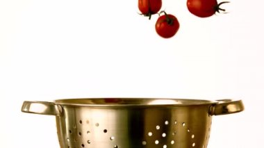 Cherry tomatoes falling into colander — Stock Video