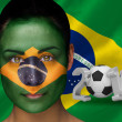 Composite image of brasil football fan in face paint — Stock Photo