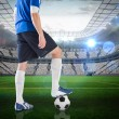 Composite image of football player standing with ball — Stock Photo