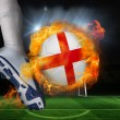 Football player kicking flaming england flag ball — Stock Photo