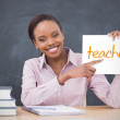 Happy teacher holding page showing teaching — Stock Photo #46747689