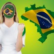 Composite image of excited brasil fan in face paint cheering — Stock Photo #46747821