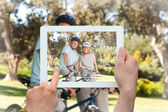 Composite image of hand holding tablet pc — Stock Photo