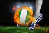 Football player kicking flaming nigeria flag ball — Stock Photo