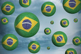 Composite image of footballs in brasil flag colours  — Stock Photo