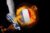 Football player kicking flaming france ball — Stock Photo