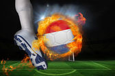 Football player kicking flaming netherlands flag ball — Stock Photo