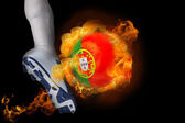 Football player kicking flaming portugal ball — Stock Photo