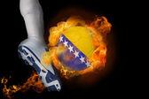 Football player kicking flaming bosnia ball — Stock Photo
