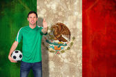 Composite image of handsome football fan in green — Stock Photo