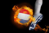 Football player kicking flaming netherlands ball — Stock Photo