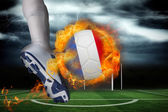 Football player kicking flaming france flag ball — Stock Photo