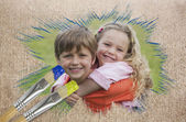 Composite image of sibling smiling in the park — Stock Photo