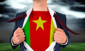 Businessman opening shirt to reveal cameroon flag — Stock Photo