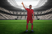 Football player in red raising his hand — Stock Photo