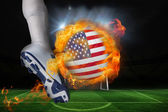 Football player kicking flaming usa flag ball — Stock Photo
