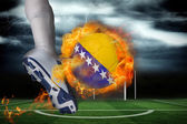 Football player kicking flaming bosnia flag ball — Stock Photo