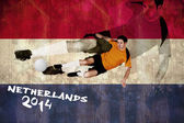 Football player in orange kicking — Stock Photo