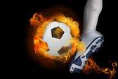 Football player kicking flaming ball — Stock Photo