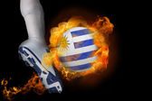 Football player kicking flaming uruguay ball — Stock Photo