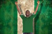 Zusammengesetztes bild jubelnder fußballfan im grünen trikot — Stockfoto