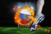 Football player kicking flaming russia flag ball — Stock Photo