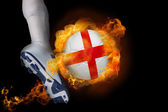 Football player kicking flaming england ball — Stock Photo