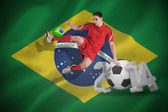 Composite image of fit football player jumping and kicking — Stock Photo