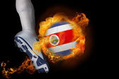 Football player kicking flaming costa rica ball — Stock Photo