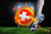Football player kicking flaming swiss flag ball — Stock Photo