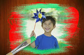 Composite image of little boy with pinwheel — Stock Photo