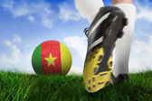 Close up of football boot kicking cameroon ball — Stock Photo