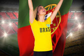 Excited football fan in brasil tshirt holding flag — Stock Photo