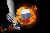 Football player kicking flaming russia ball — Stock Photo